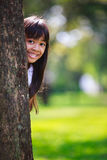 Asian little girl smiling behind a tree Royalty Free Stock Images