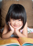 Asian little girl smiling while reading book Stock Images