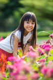 Asian little girl standing with hands on knees in a meadow Stock Images