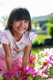 Asian little girl standing with hands on knees in a meadow, Outd Royalty Free Stock Photography