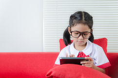 Asian little girl in student uniform using smartphone Stock Photography