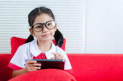 Asian little girl in student uniform using smartphone Stock Images