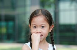 Asian little girl sucking her fingers outdoor royalty free stock photo