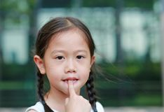 Asian little girl sucking her fingers outdoor royalty free stock images