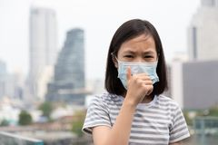 Asian little girl suffer from cough with face mask protection,cute child wearing face mask because of air pollution in the city royalty free stock photography