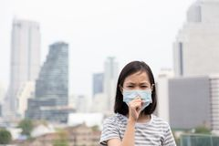 Asian little girl suffer from cough with face mask protection,cute child wearing face mask because of air pollution in the city royalty free stock images