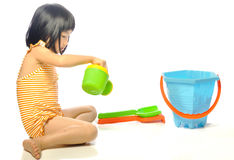 Asian little girl in swimsuit playing with beach toys on white b Stock Image