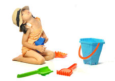 Asian little girl in swimsuit playing with beach toys on white b Royalty Free Stock Photos