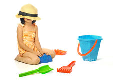 Asian little girl in swimsuit playing with beach toys on white b Stock Photos