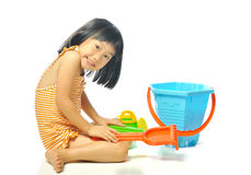 Asian little girl in swimsuit playing with beach toys Stock Photography
