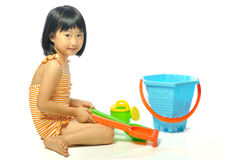 Asian little girl in swimsuit playing with beach toys Stock Photo