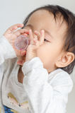 Asian little girl takes medicine syrup by herself Royalty Free Stock Image