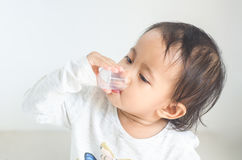 Asian little girl takes medicine syrup by herself Royalty Free Stock Photos