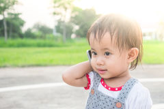 Asian little girl talking on smart phone in the park Royalty Free Stock Photos