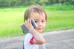Asian little girl talking on smart phone in the park Stock Photography
