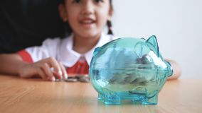 Asian little girl in Thai kindergarten student uniform putting money coin into clear piggy bank select focus on pig saving money f. Or education concept stock footage