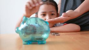 Asian little girl in Thai kindergarten student uniform putting money coin into clear piggy bank select focus on pig saving money f. Or education concept with stock footage
