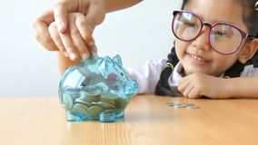 Asian little girl in Thai kindergarten student uniform putting money coin into clear piggy bank on wooden table metaphor money sav. Ing for education concept stock video