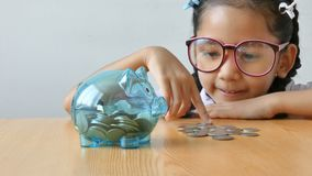 Asian little girl in Thai kindergarten student uniform putting money coin into clear piggy bank on wooden table metaphor money sav. Ing for education concept stock video footage