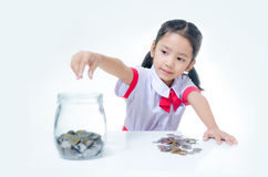Asian little girl in Thai student uniform putting coin to glass Stock Image