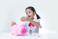 Asian little girl in Thai student uniform putting coins to piggy Royalty Free Stock Images