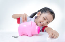 Asian little girl in Thai student uniform putting coins to piggy. Bank selective focus on hand shallow depth of field Stock Images