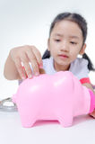Asian little girl in Thai student uniform putting coins to piggy. Bank selective focus on pig shallow depth of field Royalty Free Stock Photos