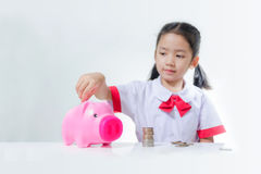 Asian little girl in Thai student uniform putting coins to piggy. Bank selective focus on pig shallow depth of field Stock Photography