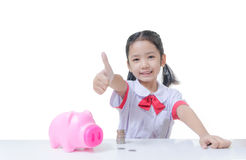 Asian little girl in Thai student uniform showing thumb up with. Asian little girl in Thai student uniform showing thumb up with piggy bank and stack of coins Stock Photo