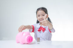Asian little girl in Thai student uniform showing thumb up with. Piggy bank and stack of coins selective focus on face shallow depth of field Royalty Free Stock Photography