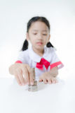 Asian little girl in Thai student uniform stacking coins Royalty Free Stock Images