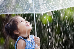 Asian little girl with umbrella in rain. Happy asian little girl with umbrella in rain Stock Photo
