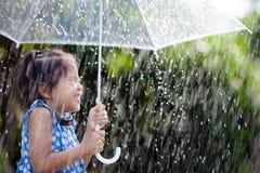 Asian little girl with umbrella in rain. Happy asian little girl with umbrella in rain Stock Image