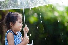 Asian little girl with umbrella in rain. Happy asian little girl with umbrella in rain Royalty Free Stock Photo