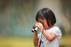 An Asian little girl using a binoculars by her own. As a background Stock Photos