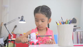 Asian little girl using the color pencil sharpener stock footage
