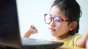 Asian little girl using laptop computer with happiness and cheerful