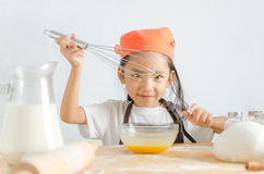 Asian little girl using stainless steel whisk to mix the egg for Stock Image