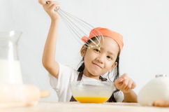 Asian little girl using stainless steel whisk to mix the egg for Stock Images