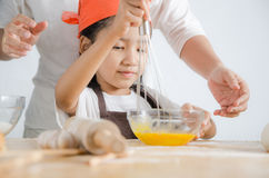 Asian little girl using stainless steel whisk to mix the egg for Royalty Free Stock Image