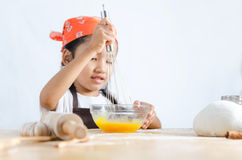 Asian little girl using stainless steel whisk to mix the egg for Stock Photos