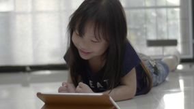 Asian little girl watching video on the digital tablet at home. stock video
