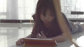 Asian little girl watching video on the digital tablet at home. stock video footage