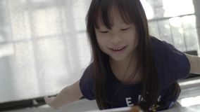 Asian little girl watching video on the digital tablet at home. stock footage