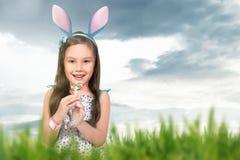 Asian little girl wearing bunny ears holding lollipop Royalty Free Stock Image