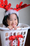 Asian little girl wearing a reindeer headband Royalty Free Stock Photo