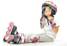 Asian little girl is wearing roller blades and protecting Stock Photos
