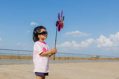 Asian little girl with wind turbine toy in hands Stock Photos