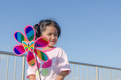 Asian little girl with wind turbine toy in hands Royalty Free Stock Photography