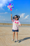 Asian little girl with wind turbine toy in hands Royalty Free Stock Image